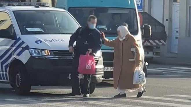 """""""Attitude noble"""" :Cette photo d'un policier bruxellois qui aide une dame est devenue virale"""